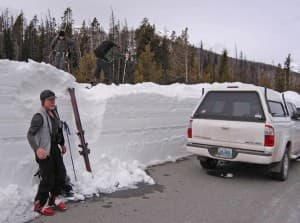 Greg Nelson, left, gathers his gear at the edge of the east entrance road in Yellowstone National Park. Phil Hawkins and Thomas Naberhaus, right, wait for him to join them as they prepare to ski to the summit of Top Notch Peak, overlooking Sylvan Pass. (Ruffin Prevost/WyoFile - click to enlarge)