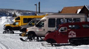 Snow coaches parked at the Old Faithful Visitor Center