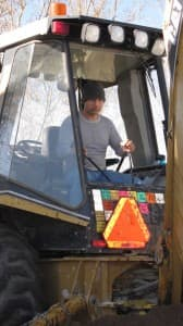 Dave Schulte of 71 Construction operates a backhoe in Casper. Employers competing for skilled workers are trying to find more affordable ways to provide health benefits. (Dustin Bleizeffer/WyoFile - click to enlarge)