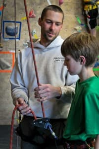BJ Tilden talks to Noah Peschio about belaying at a climbing class at Elemental Gym. (Wyofile/Kelsey Dayton)