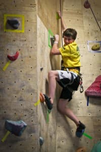 Jake Calhoun, 13, practices climbing at Elemental Performance and Fitness' climbing gym in Lander. Calhoun is part of a class taught by climber BJ Tilden meant to get Lander kids excited and interesting in rock climbing. (Wyofile/Kelsey Dayton)