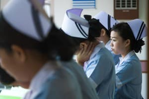Student nurses meet with their supervisor for morning instructions at Mission Hospital in Bangkok