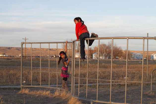 Children play on a fence outside Blue Sky Hall in Ethete. Residents say the Wind River Indian Reservation is often a more hopeful place than is portrayed in press reports