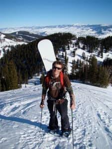 A snowboarder hikes a mountain bowl near the Grand Tetons.
