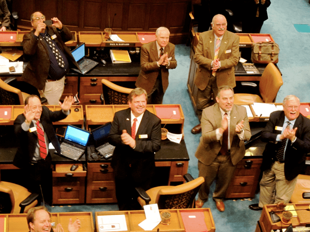 A group of Senators applaud to show their gratitude to legislative staff sitting in the third floor balcony. (WyoFile/Gregory Nickerson)