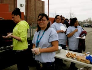 Danelle Thunder helps serve lunch to the cleanup crew outside Blue Sky Hall in Ethete.