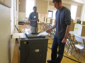 UW student Tate Anderson drops his ballot in a counting machine after voting in the primary at Lincoln Community Center in Laramie. (Gregory Nickerson/WyoFile — click to enlarge)