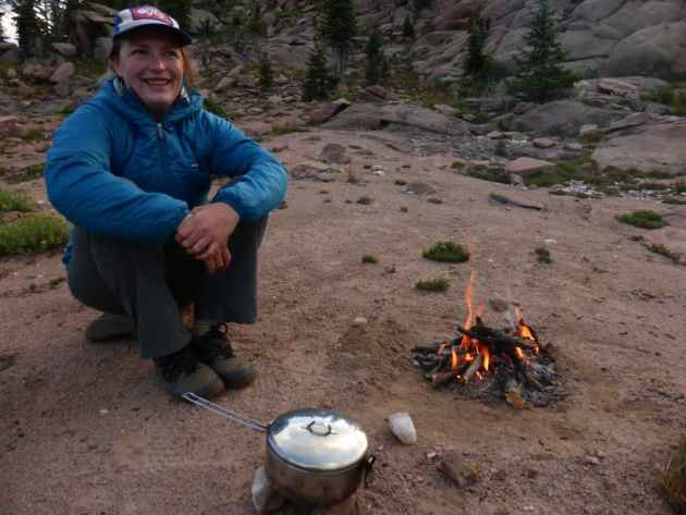 Laurel waits by the fire while split pea soup with instant mashed potatoes simmers on the alcohol stove. (Emilene Ostlind - click to enlarge)