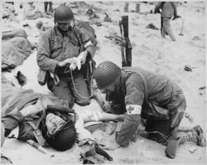 Medics treat a soldier in France during World War II. Simpson's gay cousin (not shown here) served as a medic in the European theater. (Wikimedia Commons — click to enlarge)