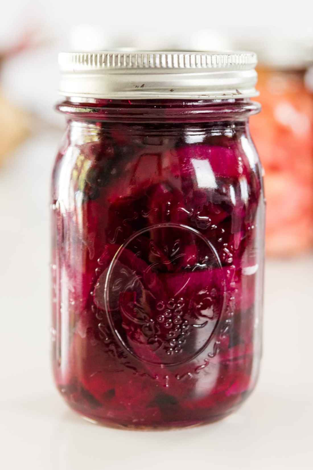 A red canned beet recipe in a Ball canning jar on a white surface with Ball canning jars in background.