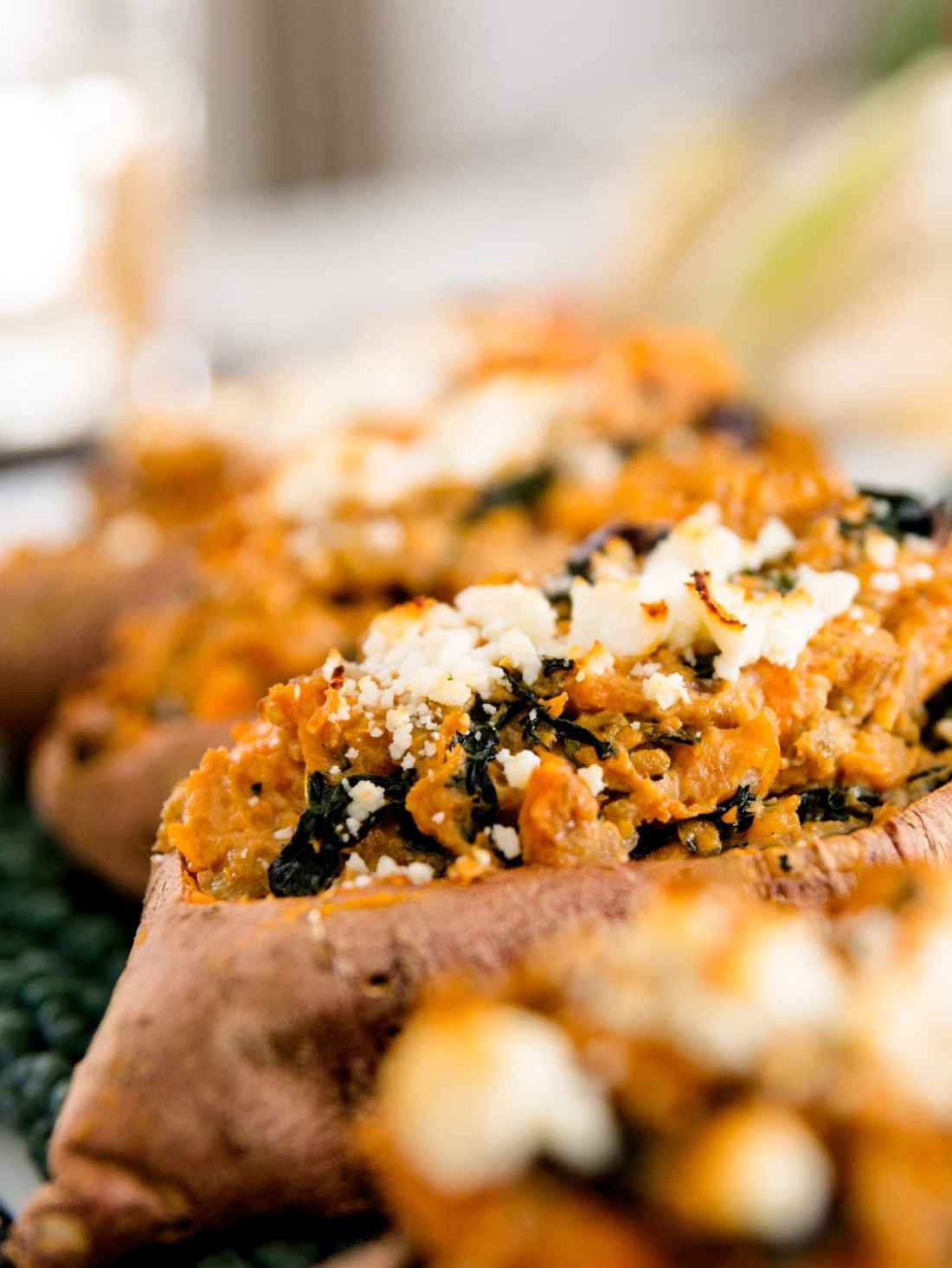 Twice baked sweet potatoes sprinkled with cheese and dotted with kale sitting on bed of kale with pumpkin in background on white surface