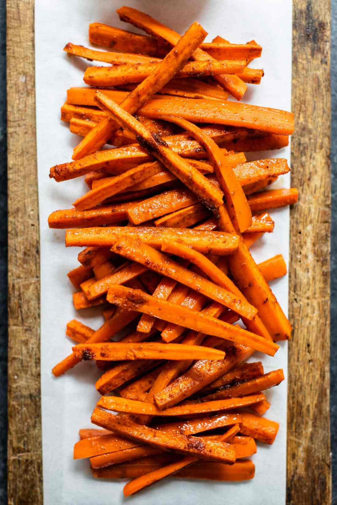 Orange harissa roasted carrots piled on a piece of parchment on a brown cutting board all on gray concrete surface
