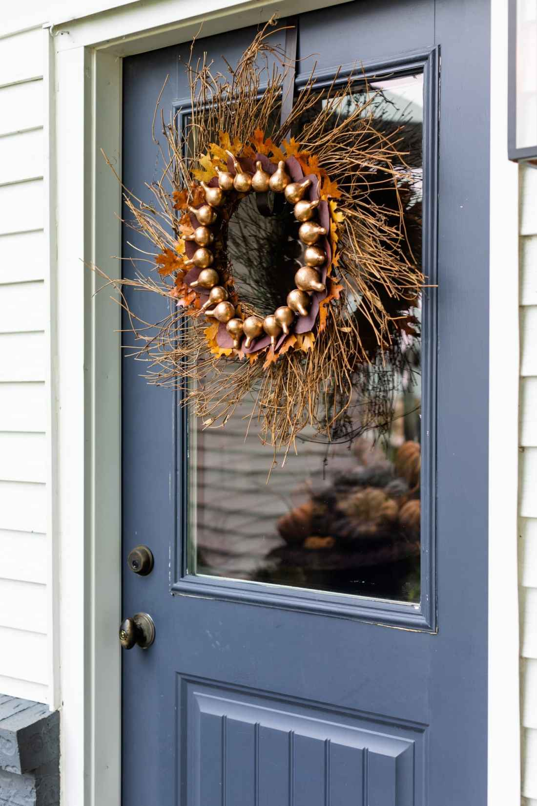 DIY fall wreath attached to a blue door with glass window full of dried gourds spray painted gold with petrified leaves attached to a grapevine wreath