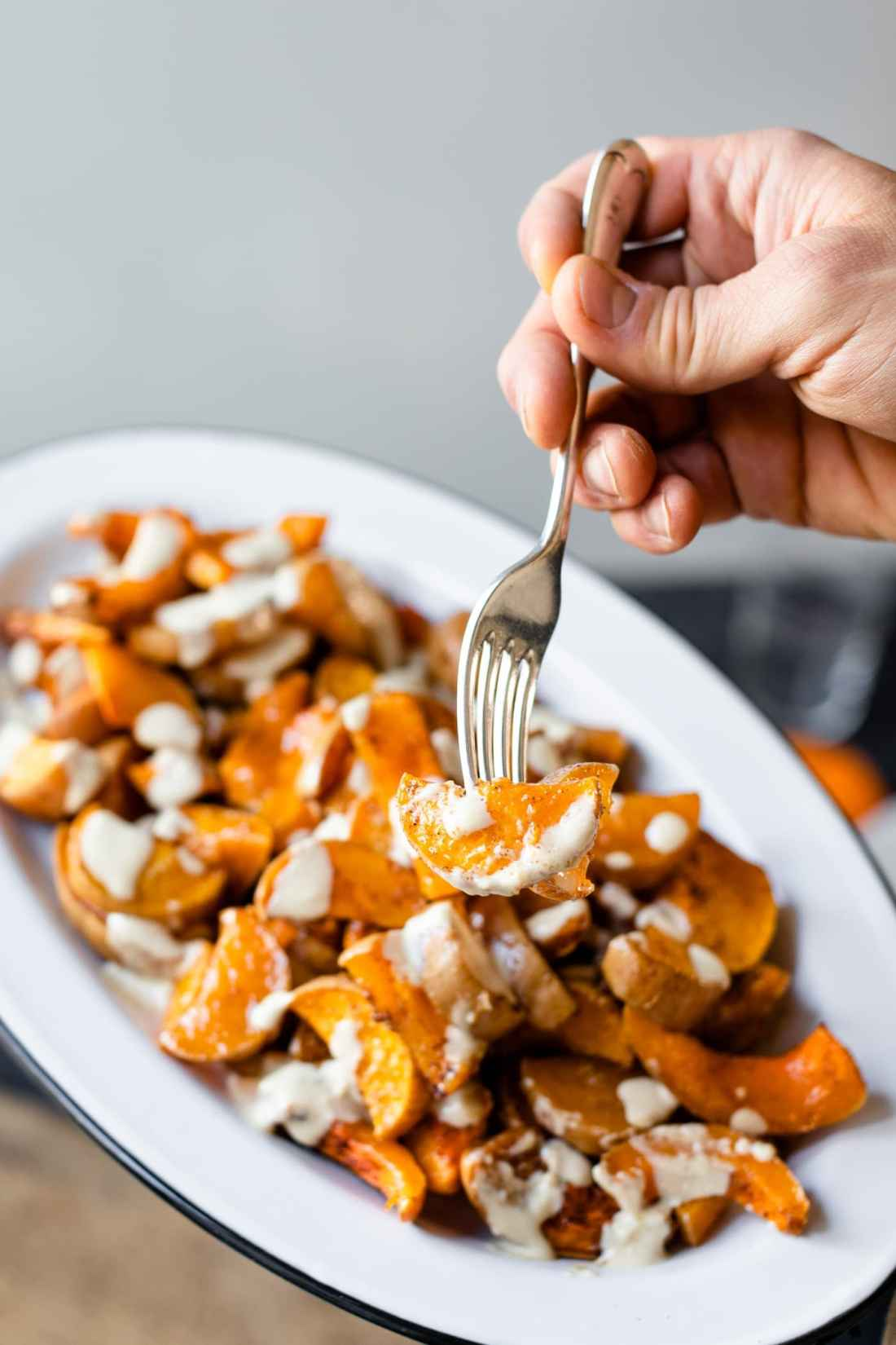 Piece of spiced butternut squash drizzled with white tahini sauce on a fork being held with platter in background on gray slate surface