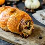 Turkey roulade sitting on wood board with pumpkins and nuts in background with linen napkin and silverware all on a gray slate surface