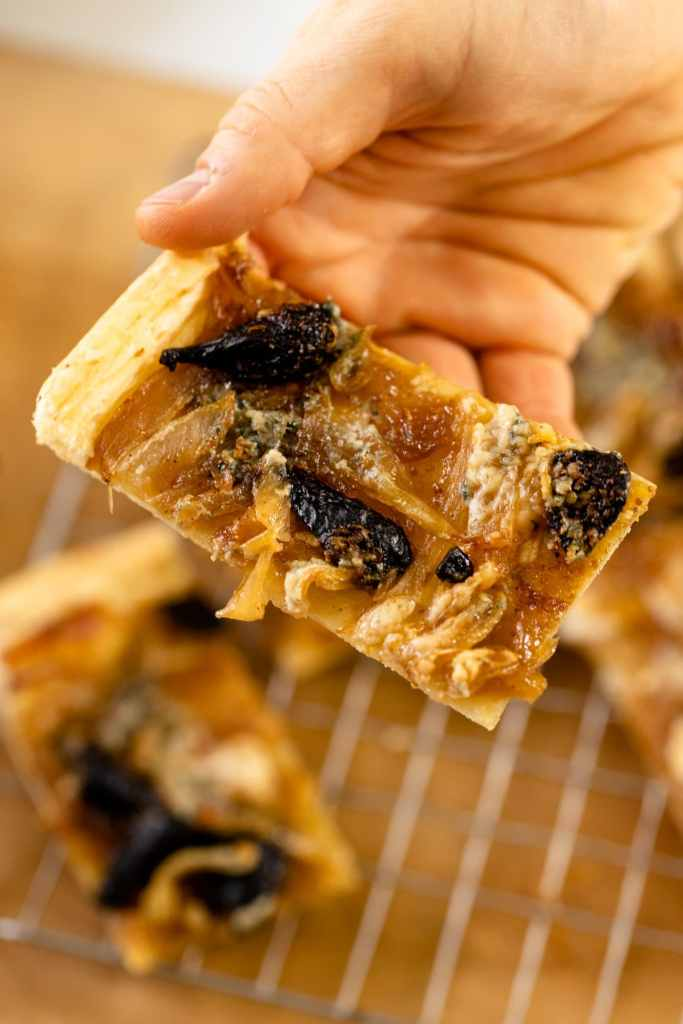 Caramelized onion tart topped with dried figs and blue cheese being held by hand with extra tarts on cooling rack on wood surface in background