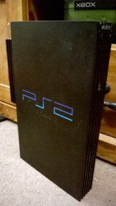 My PS2. Dusty, beaten up, and missing the Playstation emblem on the disc tray, but still working.
