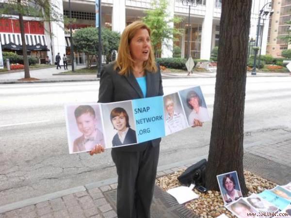 Barbara Blaine- nhà hoạt động của mạng lưới cứu trợ trẻ em bị lạm dụng tình dục,  cầm trên tay những bức hình của các nạn nhân.  Ảnh:  Mediad