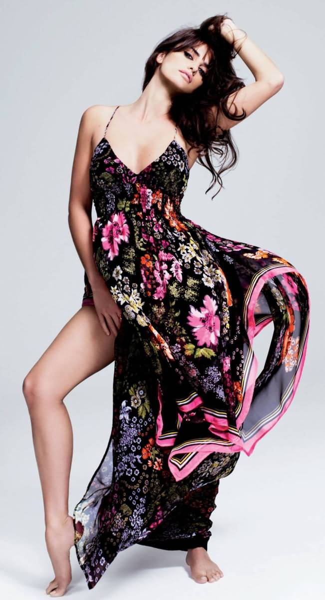 Actress Penélope Cruz poses in a long flowing floral print dress. Her left arm is reaching up to her hair and her right leg is posed out to the side showing the high slit of the dress.