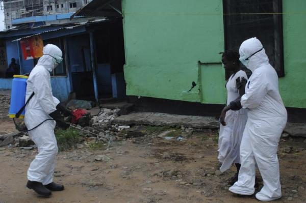 Ebola Health workers spray bleach solution on a woman suspected of having contracted the Ebola virus in Monrovia, Liberia