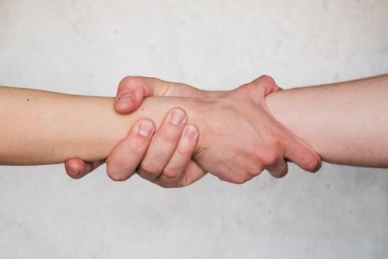 זוג שותפים נותנים יד אמיצה יד ביד