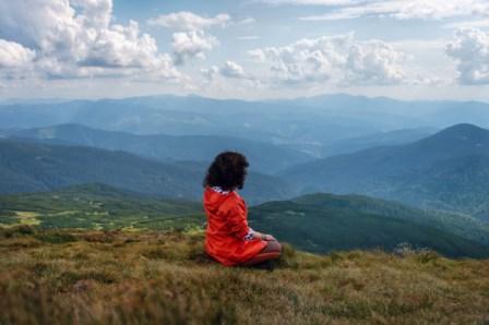 אישה מודטת לבד על רקע  נוף מדהים של ההימליה