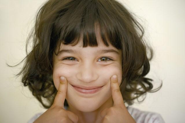 Nia estirndose los labios para mostrar sonrisa