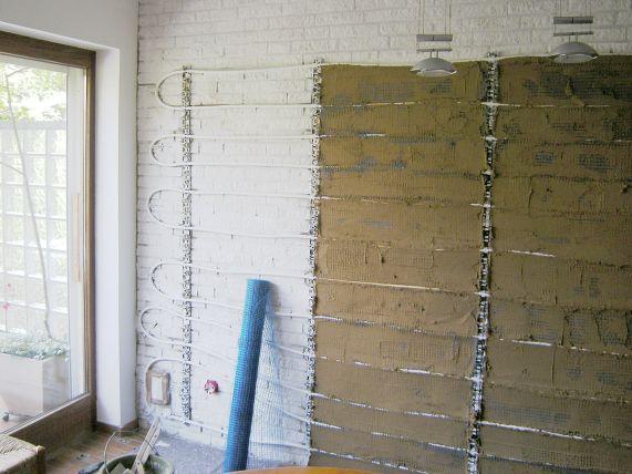Wand grundiert, Wandheizung angebaut, Lehm aufgebracht