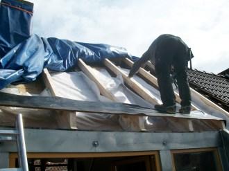 Dachsanierung von außen: Die Dampfbremse wird wannenförmig zwischen die Sparren geklebt. Innen bleiben die Flächen unberührt.