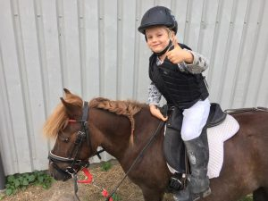Pige på hest i rideskole