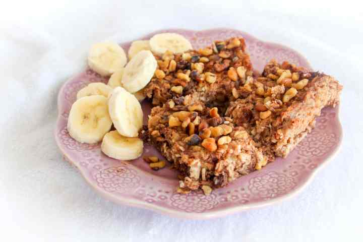 baked oatmeal on a purple plate with banana slices