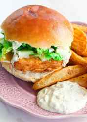 a vegetarian fish sandwich with fries on a purple plate