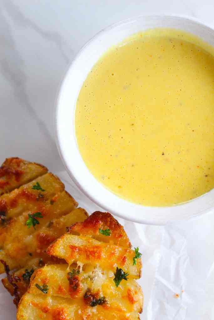 honey mustard dipping sauce with baked potatoes on a white background