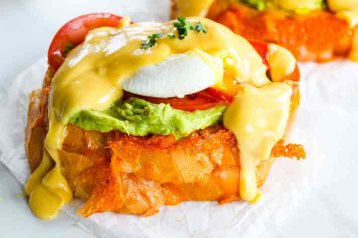 a breakfast grilled cheese Eggs Benedict sandwich on a white background