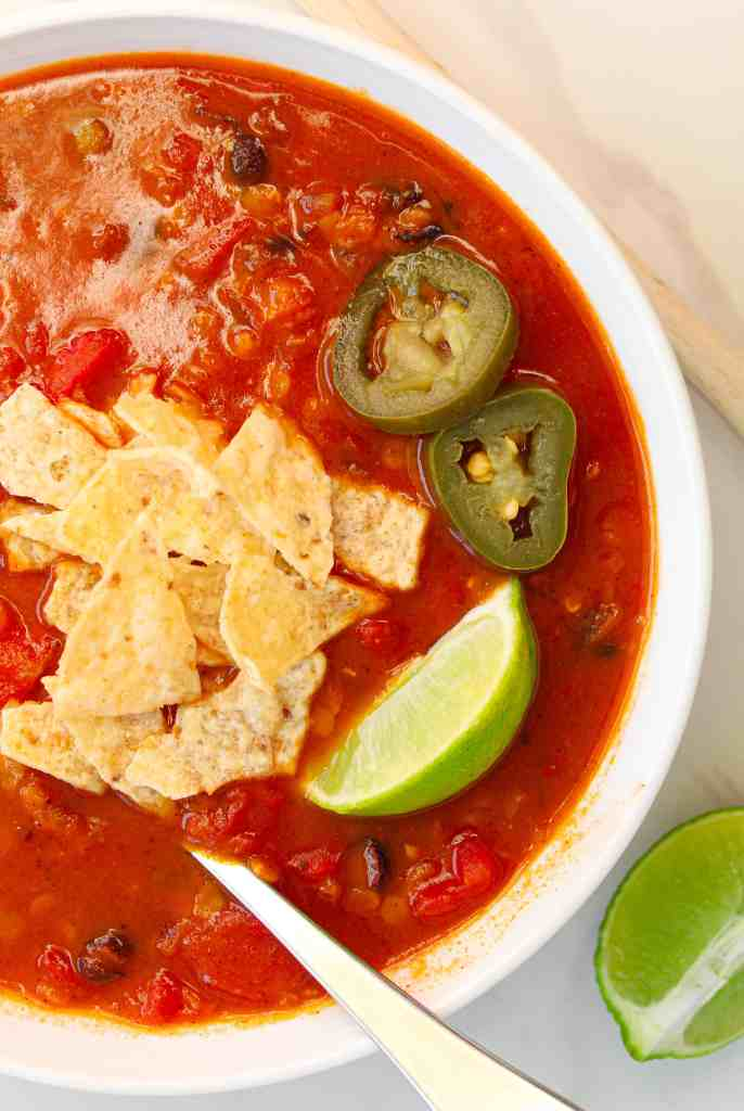 vegan lentil tortilla soup in a white bowl topped with chips and a lime