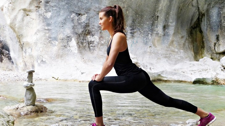 a woman stretching her legs and hips beside a river