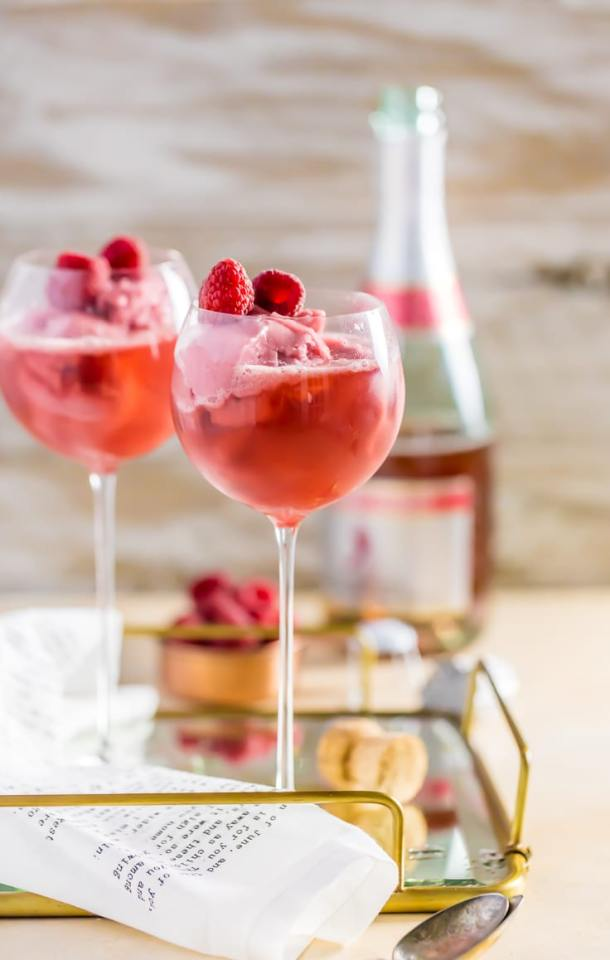 Raspberry Pink Champagne Floats | These Galentine's Day inspired cocktails are fun twists on classic cocktails that'll make your gal pal day festive! Choose from strawberry Moscow mules or homemade Frosé, cotton candy champagne or a pink senorita. These Galentine's day cocktails will elevate your next girls night! #xokatierosario #galentinesdaydrinks #girlsnightideas #girlsnightcocktails