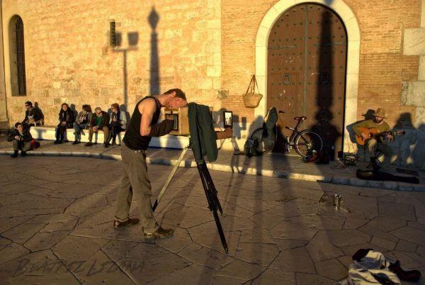 Daniel haciendo una fotografía a un guitarrista en una plaza de Sitges