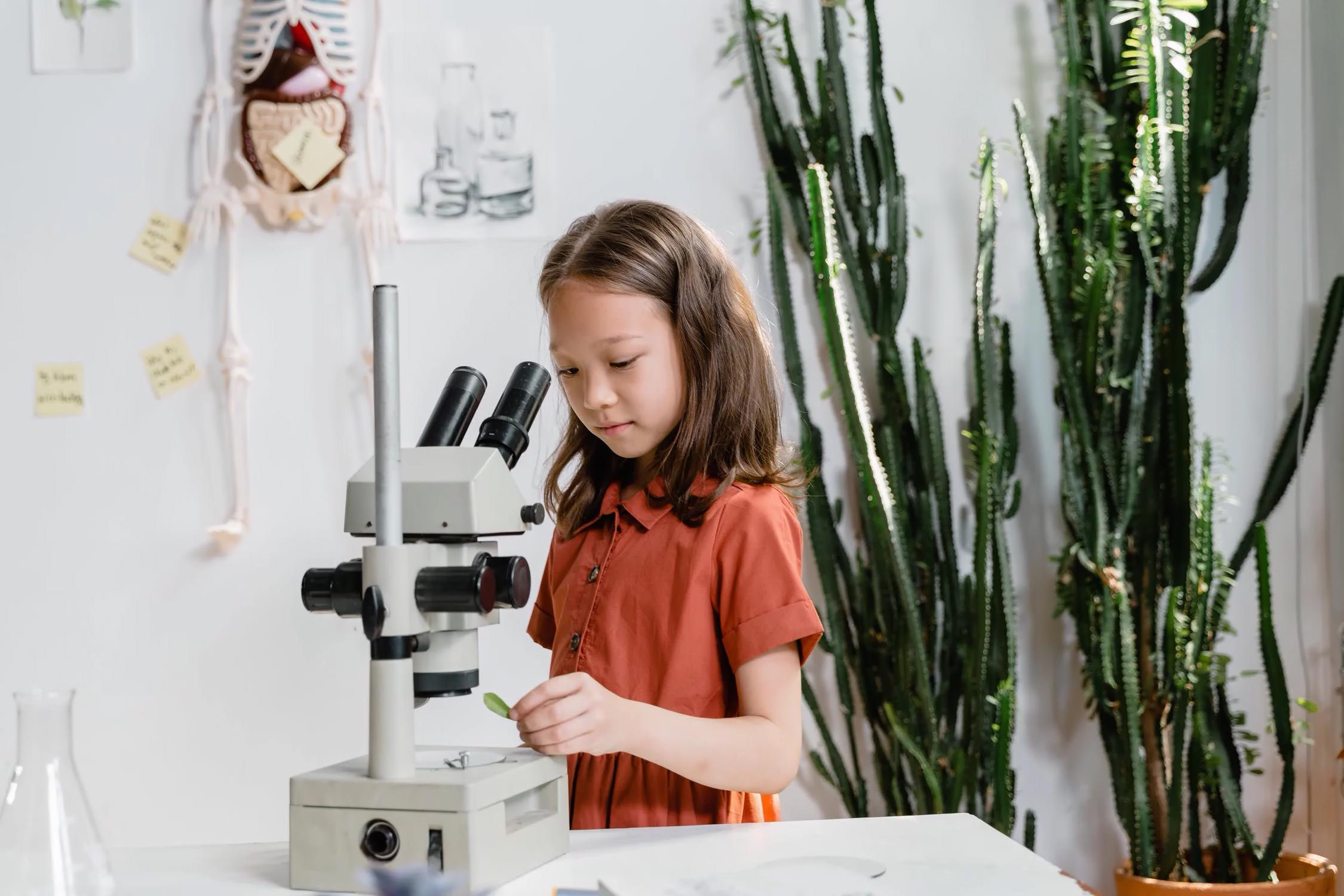 Niña explorando con microscopio