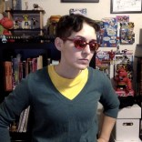 Teal v-neck sweater, yellow t-shirt, khaki pants, brown belt, red sunglasses, doofy '90s hair.