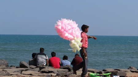 Inde du sud jeune homme vendant des barbes à papa ensachées