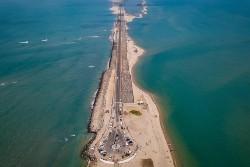 Langue de sable bordée par la mer avec une route au milieu