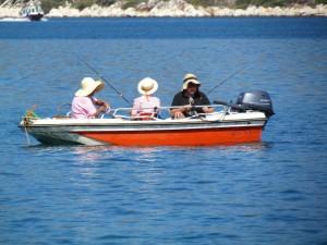 Three Greek ladies enjoying a fish in the sunshine