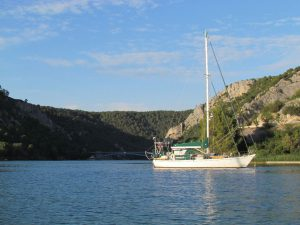 At anchor opposite Skradin, the bridge that stops any onward travel for masted boats in the background
