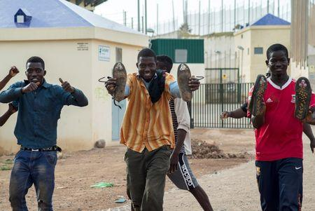 African react as they arrive at the CETI, the short-stay immigrant centre, after crossing the border from Morocco to Spain's North African enclave of Melilla