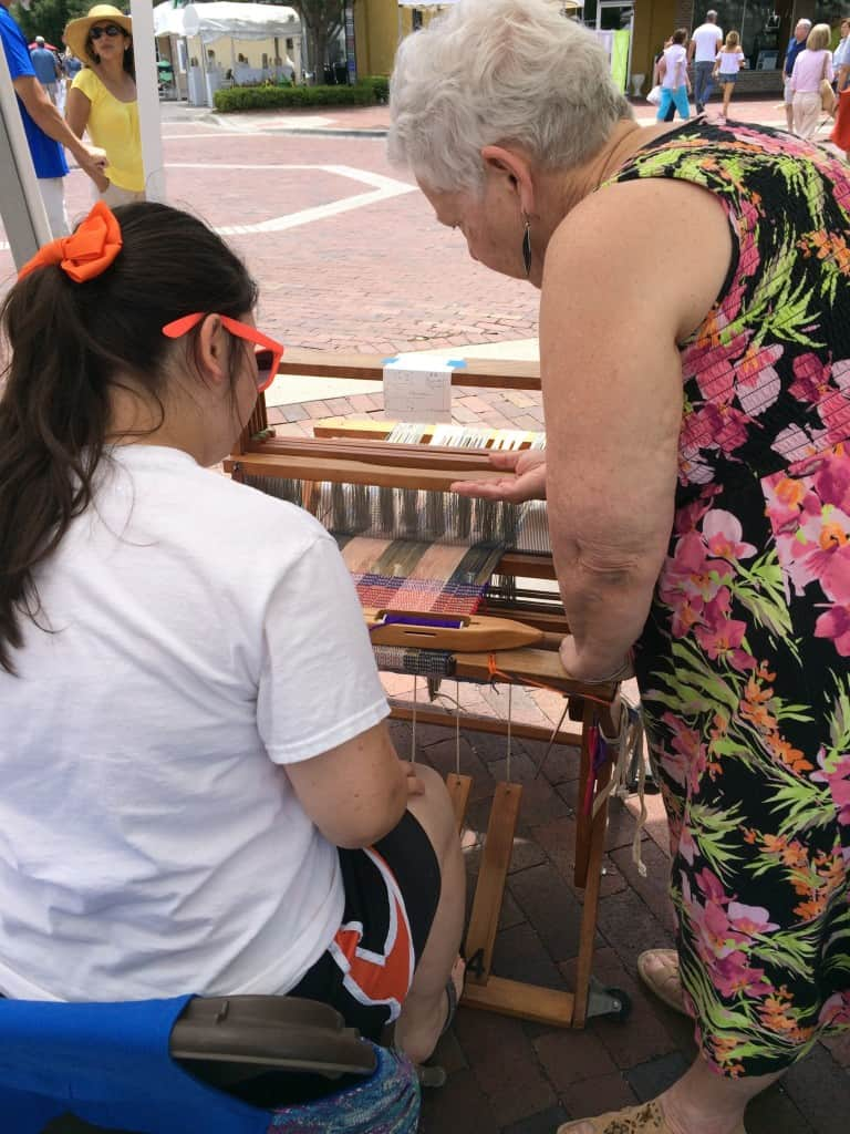 WoO member Marilyn encouraging a first-time weaver.