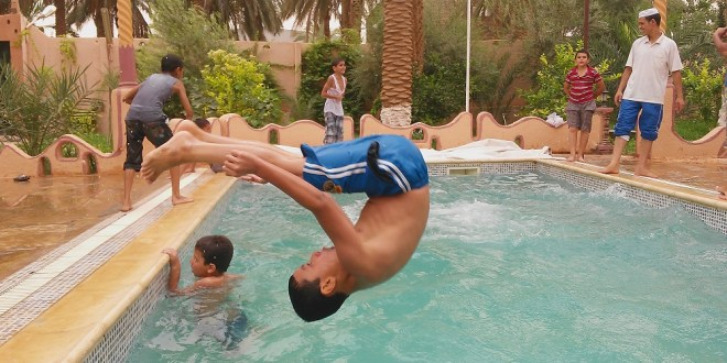 boy jumipng in the air above the water