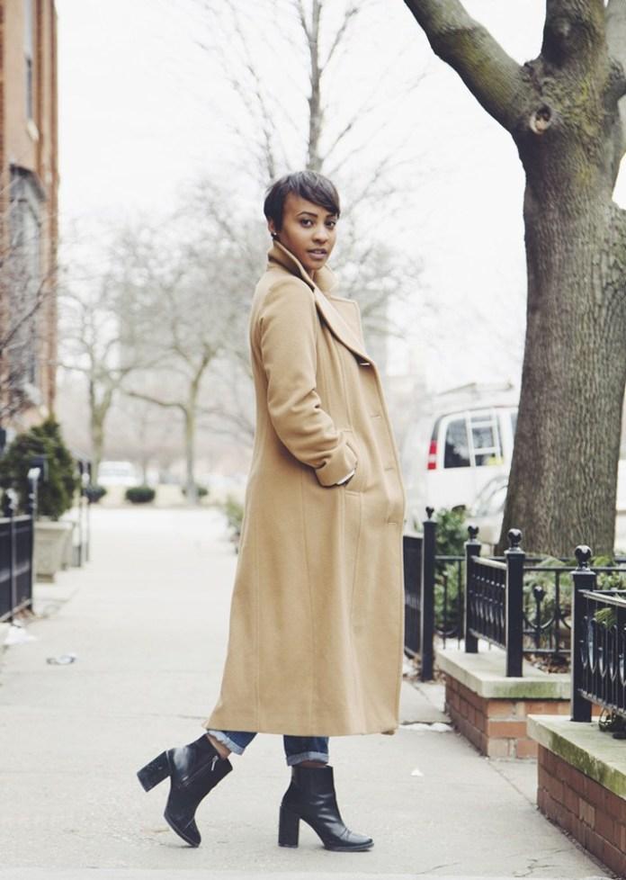 Бежевое удлиненное пальто в сочетании с длинной черной юбкой.