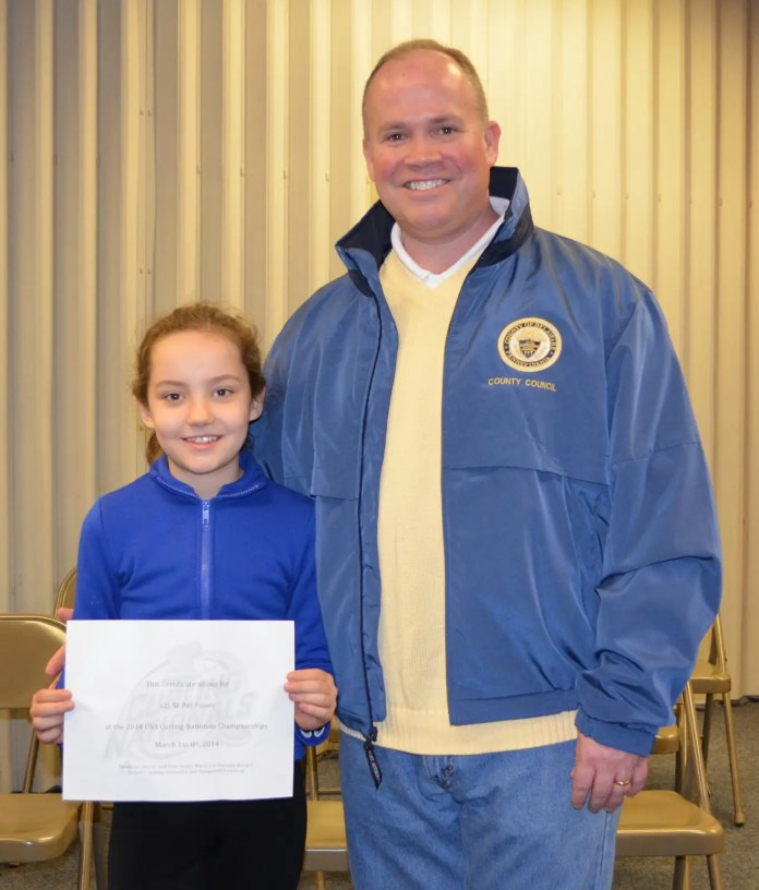 "Delaware County Councilman John McBlain presents Kristen Marvel, 9, of Malvern, with two all-day passes to the USA Curling Nationals at IceWorks, taking place March 1-8. Kristen assisted Councilman McBlain during a story time featuring the book, ""The Adventures of Trefor the Curling Rock,"" written by Kim Perkins of Calgary, Canada."