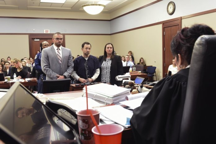 "Larry Nassar faces Ingham County Circuit Judge Rosemarie Aquilina prior to his sentencing Wednesday, Jan. 24, 2018, after the seventh day of victim impact statements in Ingham County Circuit Court in Lansing, Mich. The former sports doctor who admitted molesting some of the nation's top gymnasts for years was sentenced Wednesday to 40 to 175 years in prison as Aquilina declared: ""I just signed your death warrant."" The sentence capped a remarkable seven-day hearing in which scores of Nassar's victims were able to confront him face to face in the Michigan courtroom. (Matthew Dae Smith/Lansing State Journal via AP)"